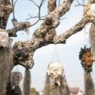 Головы разных существ висят на деревьях