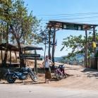 Полинка на фоне ворот в тайскую деревню
